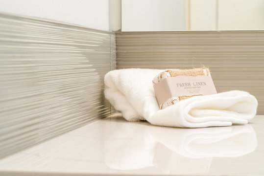 Detail of marble vanity in luxury bathroom with hand towel and soap