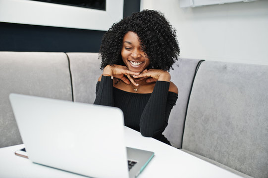 Fashionable smiled young beautiful african american business woman with afro hairstyle wear in elegant black, sitting and working at laptop.