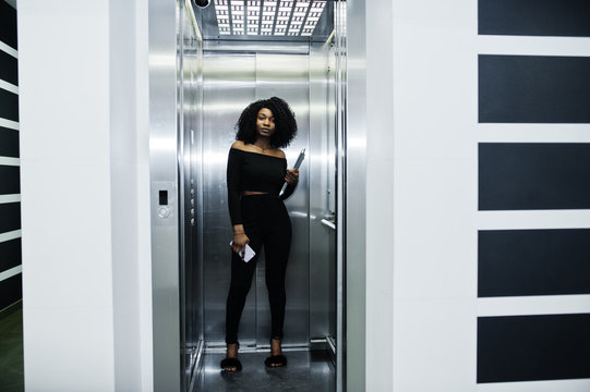 Fashionable young beautiful african american business woman with afro hairstyle wear in elegant black, stand at elevator with phone and laptop at hands.