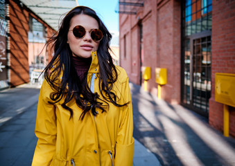 young woman in yellow raincoat at city street