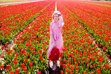 Smiling teenage girl walks through tulip field
