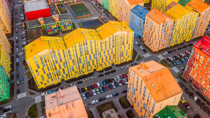 panoramic aerial view of colorful (red, green, blue, yellow) buildings on city street. drone shot