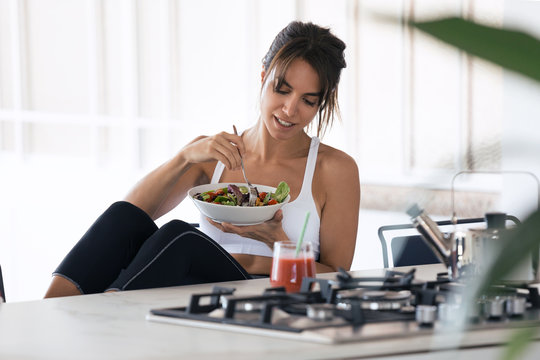 Sporty young woman eating salad and drinking fruit juice in the kitchen at home.