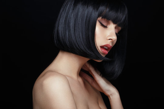 Profile portrait of a sensual young woman in black wig, bob haircuts, she touches his neck, have closed eyes, make up, big lips, naked shoulders, isolated on a black background.
