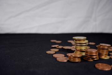 Monete posizionate in pile a destra dell'immagine con sfondo nero e bianco