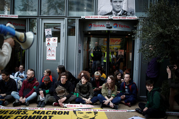 """Environmental activists block the entrance to the headquarters of French oil giant Total during a """"civil disobedience action"""" to urge world leaders to act against climate change, in La Defense near Paris"""