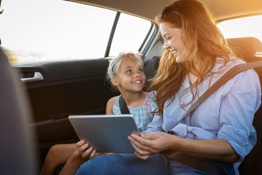Mother and daughter using digital tablet in car