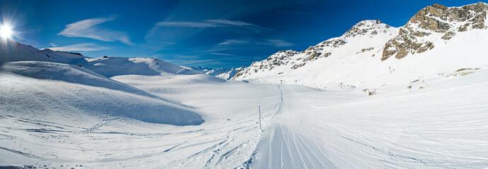 Wall Mural - Skiers on a piste in alpine ski resort