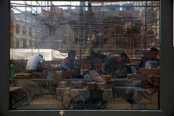 Craftsmen work to rebuild wooden structures of a temple damaged during the 2015 earthquake at Patan Durbar Square, a UNESCO world heritage site, in Lalitpur