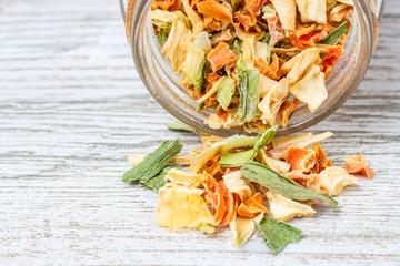 Liofilizowane warzywa. Przyprawa z suszonych warzyw wysypana na drewniany blat.