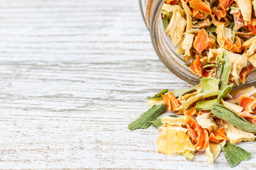 Przyprawa z suszonych warzyw wysypana na drewniany blat.  Liofilizowane warzywa i wolna przestrzeń.
