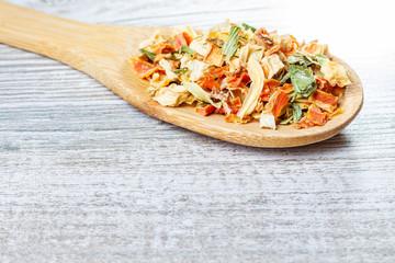 Przyprawy i suszone warzywa leżące na drewnianej łyżce. Liofilizowane warzywa.