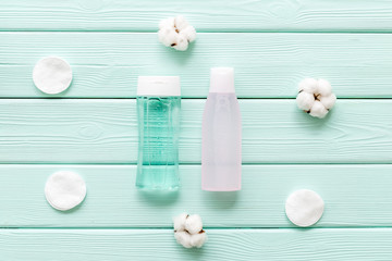 Cosmetics for face clearing with cotton pads, facial tonic and mycelial water mint green background top view mockup