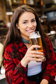 Girl having a beer while waiting for a friend. Long haired woman drinking beer at a bar. Girl in a flannel shirt at a bar.