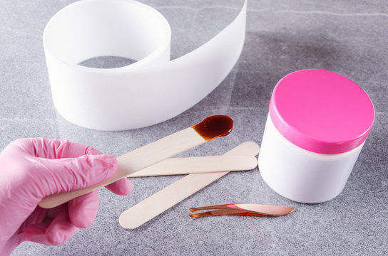 Cosmetologist in pink protective gloves holding stick with wax for depilation.Concept of preparation for waxing treatments