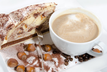 Slice of gourmet fresh hazelnut cholcolate cake on a plate with  fresh hazelnuts and coffee beans in a close up view on a plate with a cup of coffee