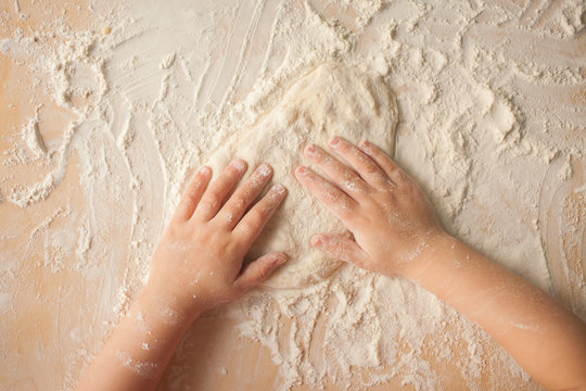 Making dough by child hands at home. Top view