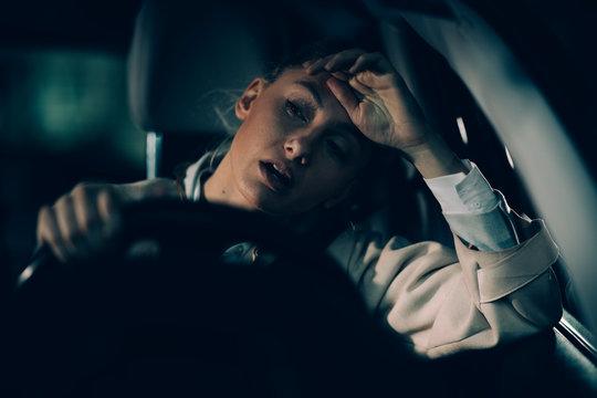 Woman annoyed in car. Girl stuck in traffic.