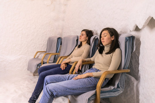 Two Women Sitting With Closed Eyes In Chairs, Relaxing In A Salt Cave At Halotherapy Session, Breathing Salt Aerosol