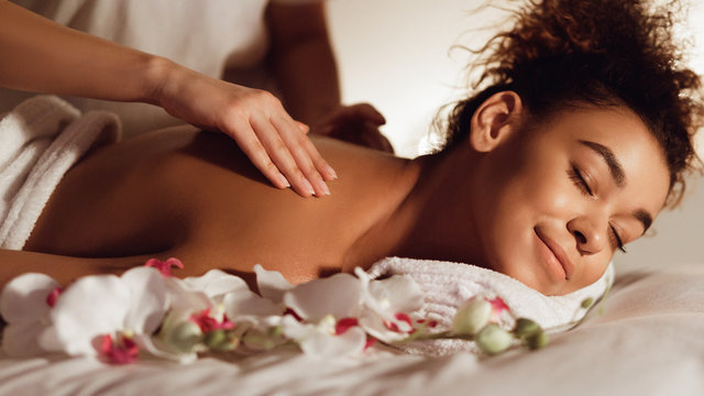 Relaxed woman getting back massage in spa center