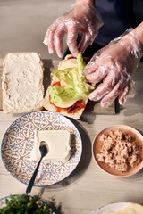 Chef's hands in gloves putting layers of ingredients on big appetizing sandwich. Decorating with green salad leaves. Components of dish in plates on light wooden background. Close up top view.