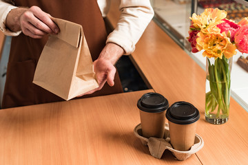Partial view of barista in brown apron with paper bag and coffee to go