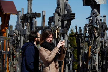 A woman takes a picture at the Hill of Crosses during Easter celebrations, near Siauliai
