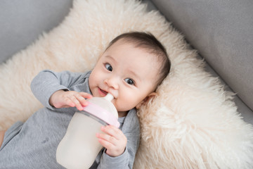Asian baby infant eating milk from bottle, 9 months after birth