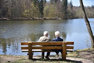 Senioren Paar sitzt auf einer Parkbank am See im Park