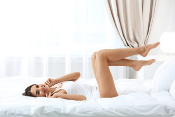 Young woman with perfect smooth skin in bedroom. Beauty and body care