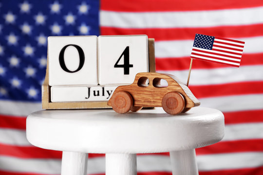 Composition with calendar and wooden car on stool against USA flag