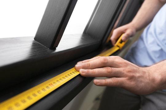 Man measuring wooden window frame indoors, closeup. Construction tool