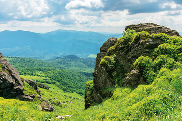 summer nature landscape in mountains. huge boulders on the edge of a grassy slope. ridge behind the valley in the distance. sunny weather with cloudy sky. beautiful carpathian scenery
