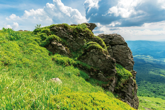 summer nature scenery in mountains. huge rocky formation on the edge of a grassy slope. view in to the distant valley. sunny weather with cloudy sky.