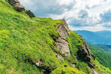 summer landscape in carpathian mountains. huge rocky formation on the edge of a grassy slope. ridge behind the valley in the distance. sunny weather with cloudy sky.