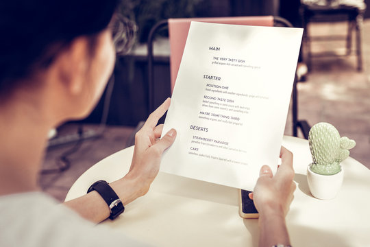 Close up of a menu being in female hands