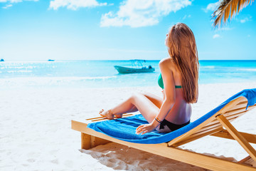 Holiday vacation beach - beautiful young girl relaxing on lounger on paradise caribbean beach with white sand and palms near blue sea on warm summer day