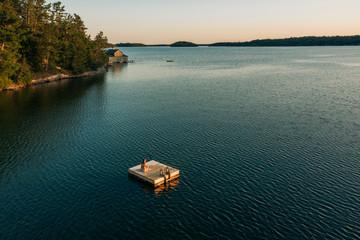 Woman on dock on lake, Muskoka, Canada