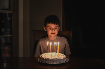 Young boy looking at candles on his birthday cake