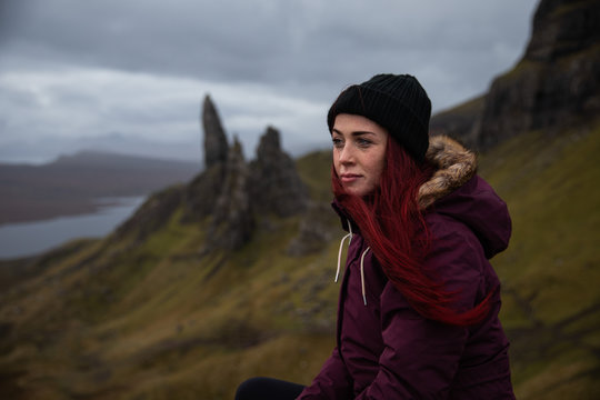 Young woman looking at The Storr, Isle of Skye, Scotland, UK