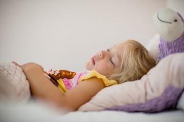 toddler girl sleeping on back in bed