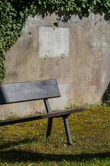 Leere Sitzbank vor leerer Grabstätte
