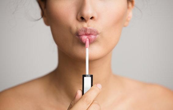Young woman applying lip gloss on her lips