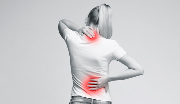 Woman rubbing her painful neck and back