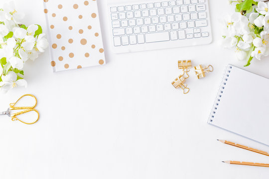 Flat lay blogger or freelancer workspace with a notebook, keyboard and white spring flowers on a white table