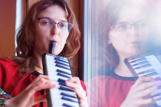 The girl plays melodica. In the hands of a woman musical instrument harmonica. The musician stands at the window. Harmonica with piano keys.