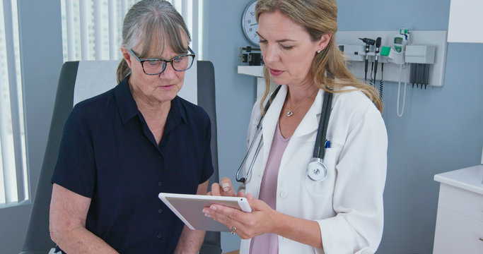 Female primary care physician having conversation with older Caucasian woman during regular check up. Senior patient talking with her reassuring doctor in exam room