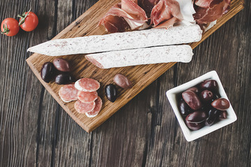 Italian salami, prosciutto, olives on a brown wooden board.  Mediterranean kitchen.
