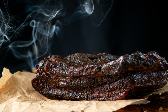 Smoked Pork Brisket BBQ with a dark bark on a wooden  board from the classic Texas smokehouse
