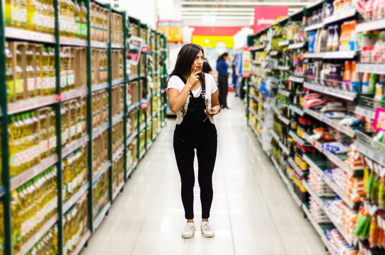 Thoughtful woman doing house shopping for pantry in supermarket